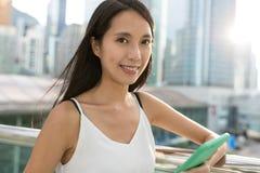 Mujer asiática joven que sostiene el teléfono móvil en la ciudad Imagen de archivo libre de regalías