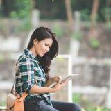 Mujer asiática joven que sostiene una PC de la tableta mientras que se sienta en el parque Foto de archivo