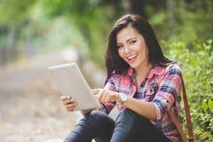 Mujer asiática joven que sostiene una PC de la tableta mientras que se sienta en el parque Imágenes de archivo libres de regalías