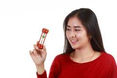 Mujer asiática joven que sostiene y que mira el reloj de arena con la sonrisa Imagenes de archivo