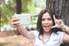 Mujer asiática joven que toma un selfie mientras que se sienta al aire libre en un par Fotografía de archivo libre de regalías