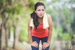 Mujer asiática joven que toma una rotura después de correr en el parque Fotos de archivo
