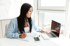 Mujer asiática joven que trabaja con el ordenador portátil y que toma notas Imagen de archivo libre de regalías