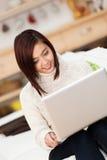 Mujer asiática joven que trabaja en un ordenador portátil Foto de archivo libre de regalías