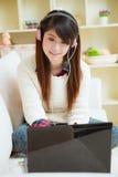 Mujer asiática joven que usa el ordenador portátil Imagenes de archivo