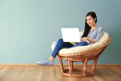 Mujer asiática joven que usa el ordenador portátil en sillón Fotografía de archivo