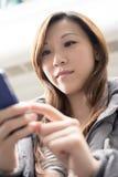 Mujer asiática joven que usa el teléfono móvil foto de archivo libre de regalías