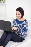 Mujer asiática joven que usa la computadora portátil Imagen de archivo
