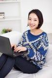 Mujer asiática joven que usa la computadora portátil Foto de archivo
