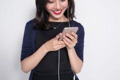 Mujer asiática joven que usa smartphone en blanco Foto de archivo