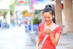 Mujer asiática joven que usa su teléfono elegante al aire libre Fotografía de archivo libre de regalías