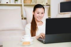 Mujer asiática joven que usa un ordenador portátil Imágenes de archivo libres de regalías