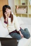 Mujer asiática joven que usa un ordenador portátil y un teléfono móvil Imagen de archivo