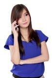 Mujer asiática joven que usa un teléfono móvil, aislado en blanco Fotos de archivo libres de regalías