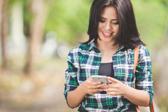 Mujer asiática joven que usa un teléfono móvil mientras que camina en el parque Imagenes de archivo