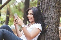 Mujer asiática joven que usa un teléfono móvil mientras que se sienta al aire libre en un p Imagen de archivo