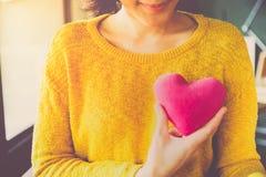 Mujer asiática joven romántica con la almohada en forma de corazón rosada imagen de archivo