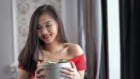 Mujer asiática joven romántica que sonríe y que sostiene el primer medio de la caja de regalo