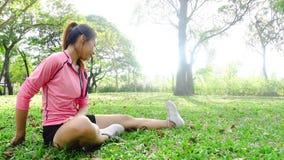 Mujer asiática joven sana que ejercita en el parque Mujer joven apta que hace entrenamiento del entrenamiento por mañana almacen de metraje de vídeo