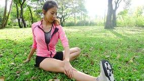 Mujer asiática joven sana que ejercita en el parque Mujer joven apta que hace entrenamiento del entrenamiento por mañana metrajes