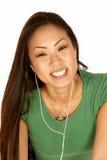 Mujer asiática joven sonriente con los brotes del oído imagen de archivo libre de regalías