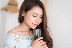Mujer asiática joven sonriente que bebe el jugo verde o de las verduras frescas fotos de archivo
