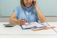 Mujer asiática joven sonriente que habla en el teléfono móvil fotos de archivo libres de regalías