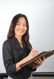 Mujer asiática joven sonriente que hace notas Foto de archivo
