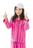 Mujer asiática joven sonriente que muestra el pulgar encima de la muestra con ambas manos Imagen de archivo