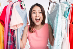 Mujer asiática joven sorprendida en la tienda, mirando a escondidas hacia fuera a través de clothin Fotos de archivo