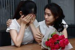 Mujer asiática joven subrayada que apoya al amigo femenino gritador presionado en sala de estar Rómpase para arriba o el mejor co Imagen de archivo libre de regalías