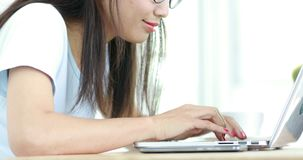 Mujer asiática linda joven que usa el ordenador portátil y pensando en eso almacen de video