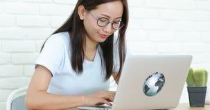 Mujer asiática linda joven que usa el ordenador portátil y pensando en eso metrajes