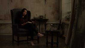 Mujer asiática linda que lee un libro en interior retro metrajes