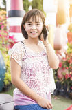 Mujer asiática madura atractiva que llama por teléfono en casa en jardín fotos de archivo