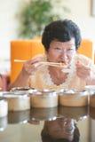 Mujer asiática mayor que cena en el restaurante Imagen de archivo libre de regalías