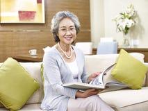 Mujer asiática mayor que lee un libro Foto de archivo libre de regalías