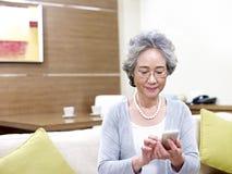 Mujer asiática mayor que usa el teléfono móvil Foto de archivo libre de regalías