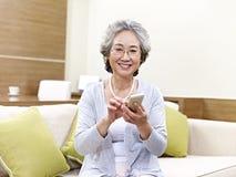 Mujer asiática mayor que usa el teléfono móvil Fotos de archivo libres de regalías