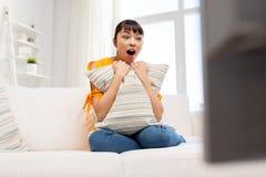 Mujer asiática pasmada con ver la TV en casa Fotografía de archivo