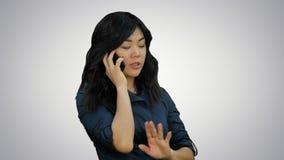 Mujer asiática positiva y feliz que habla en un teléfono celular en el fondo blanco metrajes