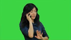 Mujer asiática positiva y feliz que habla en un teléfono celular en una pantalla verde, llave de la croma almacen de video