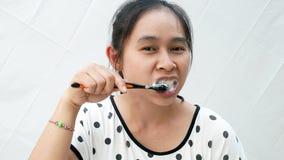 Mujer asiática que acaba de despertar cepillado sus dientes con la situación de la somnolencia sobre el fondo blanco almacen de video
