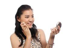 Mujer asiática que aplica maquillaje en cara Fotografía de archivo