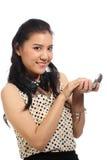 Mujer asiática que aplica maquillaje en cara Foto de archivo