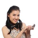Mujer asiática que aplica maquillaje en cara Imágenes de archivo libres de regalías