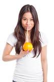 Mujer asiática que bebe el zumo de naranja Foto de archivo libre de regalías
