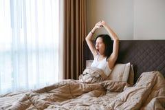 Mujer asiática que bosteza y que despierta en cama en dormitorio de lujo en th Imagen de archivo libre de regalías