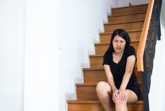 Mujer asiática que cae abajo de la escalera, hembra de las manos que toca su pierna herida Imagen de archivo