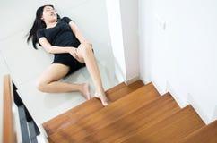 Mujer asiática que cae abajo de la escalera, hembra de las manos que toca su pierna herida Imágenes de archivo libres de regalías